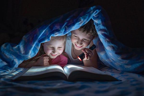 bambini sotto la coperta leggono