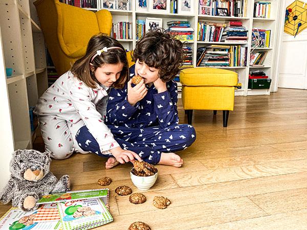 bambini in pigiama mangiano biscotti